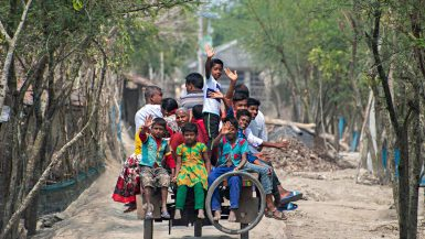 attimi di vita in un villaggio della foresta del Bengala, persone ammassate su un carretto salutano felici