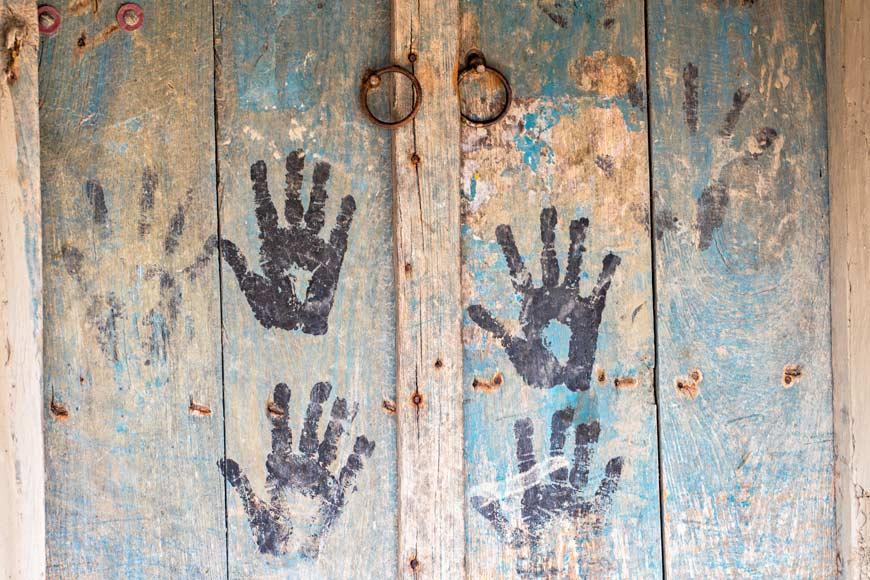 In questa immagine ci sono diverse impronte impresse su un portone. Impossibile identificarne il sesso, etnia e religione. Siamo tutti uguali!  Un'immagine forte che fa riflettere sul razzismo. Siamo davvero fatti così?