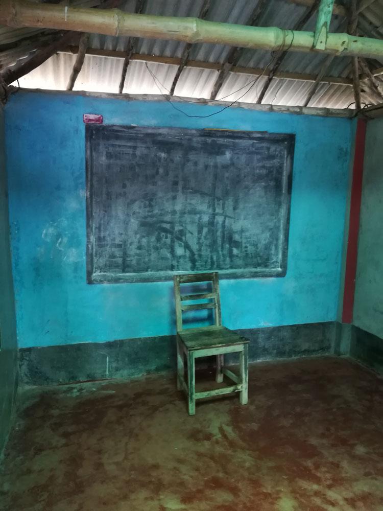Una lavagna appesa su una parete blu e una sedia a fare da cattedra al maestro della scuola