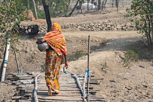 Una donna che và a prendere acqua nei villaggi con la tipica brocca di metallo utilizzata in quest'area