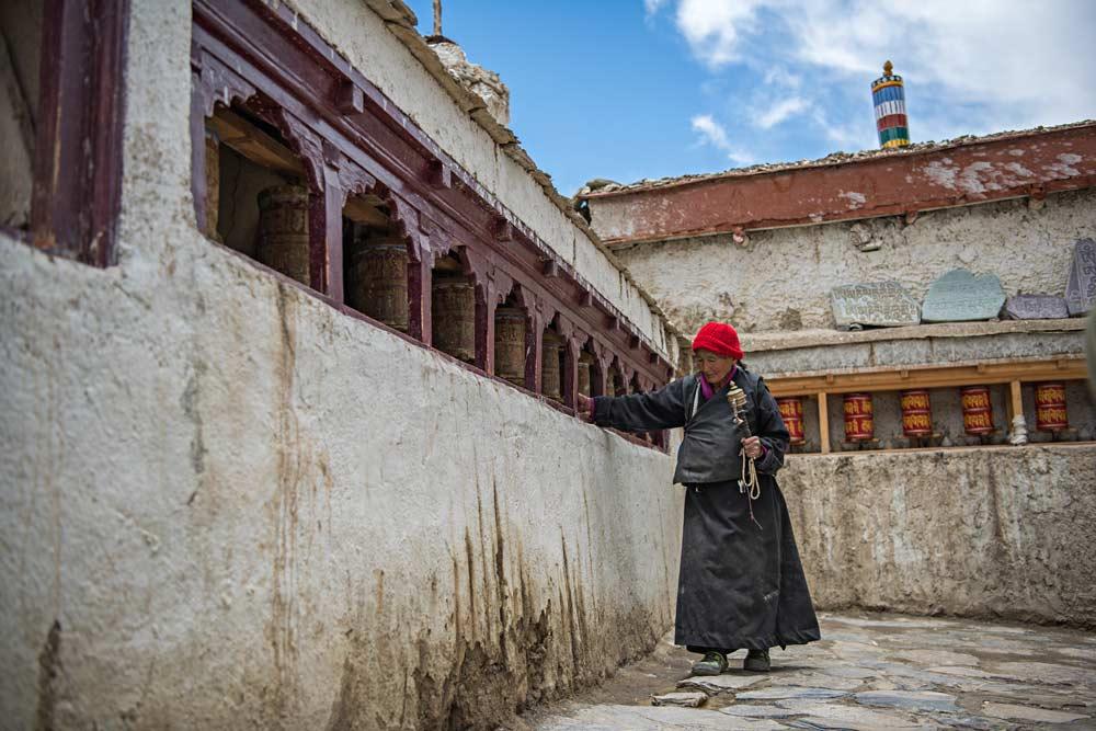 Una devota buddista stringe a sé una mala e una ruota di preghiera durante il pellegrinaggio in un monastero in Ladakh